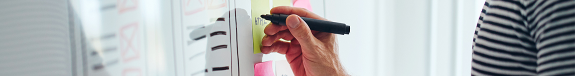 hand-holding-marker-writing-on-white-board