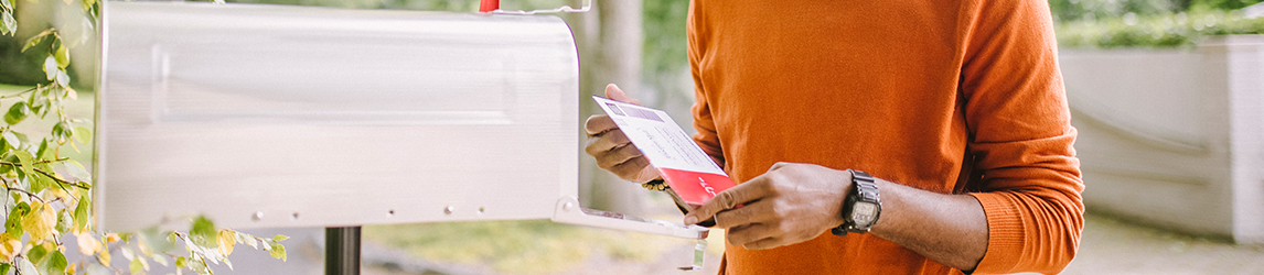 man-looks-at-letter-by-mailbox-1